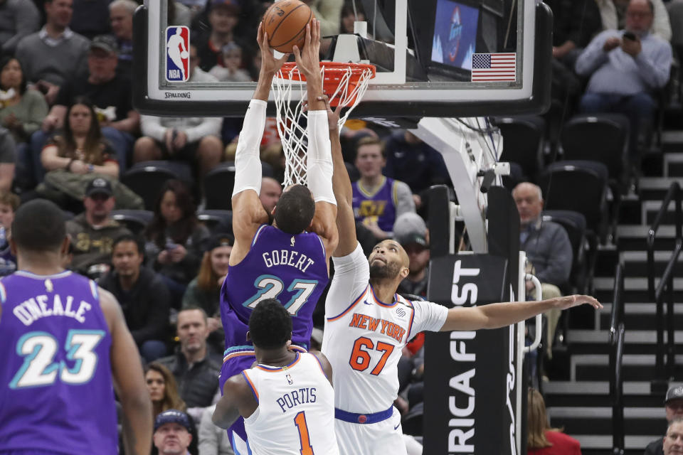 Utah Jazz center Rudy Gobert (27) is fouled by New York Knicks forward Taj Gibson (67) while shooting during the first quarter of an NBA basketball game Wednesday, Jan. 8, 2020, in Salt Lake City. (AP Photo/Chris Nicoll)