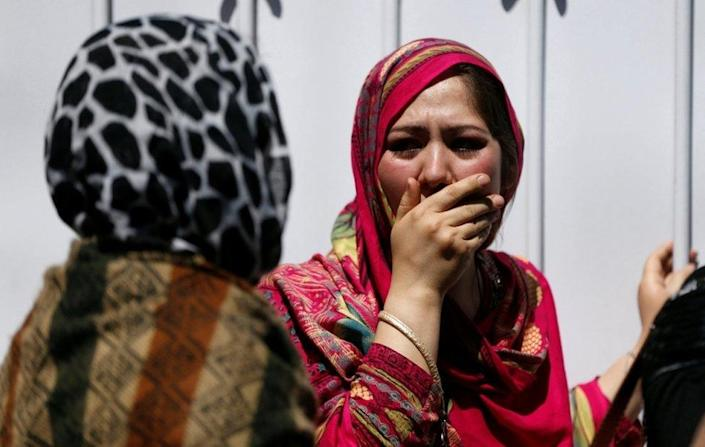 Bereaved women cover their faces in shock outside a hospital after a truck-bomb attack in Kabul on 31 May 2017
