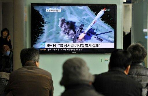 South Korean people watch a TV screen showing a graphic of North Korea's rocket launch in Seoul on April 2012