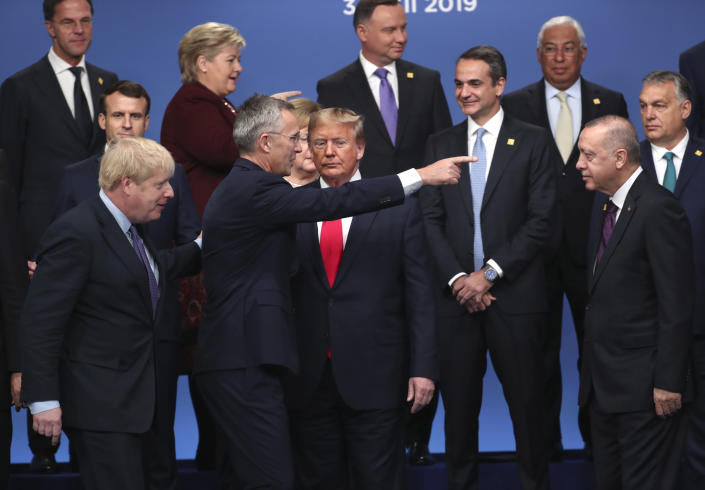FILE - In this Wednesday, Dec. 4, 2019 file photo Britain's Prime Minister Boris Johnson, left, looks on as NATO Secretary General Jens Stoltenberg, center front left, speaks with U.S. President Donald Trump, center front right, during a ceremony event at a NATO leaders meeting at The Grove hotel and resort in Watford, Hertfordshire, England. (AP Photo/Francisco Seco, File)