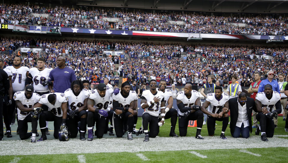 Baltimore Ravens players, including former player Ray Lewis, second from right, kneel during the playing of the U.S. national anthem before an NFL football game against the Jacksonville Jaguars at Wembley Stadium in London. (AP)
