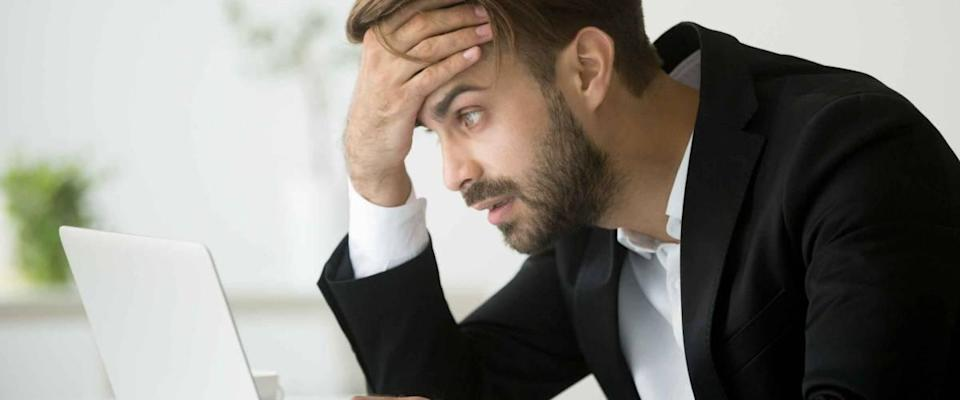 Worried stressed businessman in suit shocked by bad news using laptop