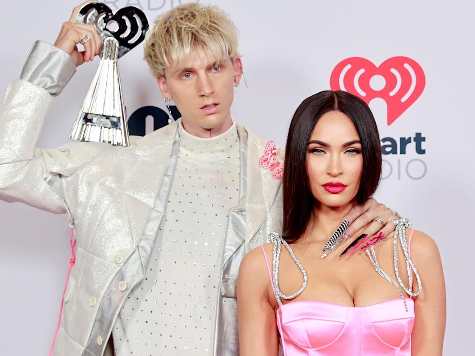 Rapper Machine Gun Kelly wears a white and silver suit and holds an iHeart Radio Music award while posing with his hand on girlfriend Megan Fox's neck, who is wearing a pink satin jumpsuit and staring at the camera.