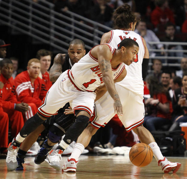 Chicago Bulls guard Derrick Rose (1) escapes the defense of Orlando Magic guard Jameer Nelson on a pick set by center Joakim Noah during the first half of an NBA basketball game Thursday, March 8, 2012, in Chicago. (AP Photo/Charles Rex Arbogast)