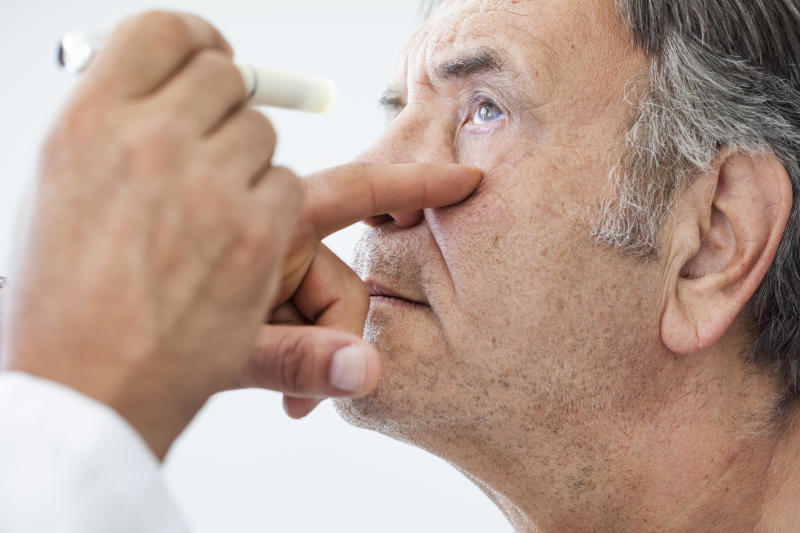 An elderly man having an eye exam.