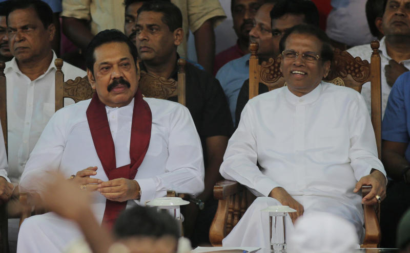 FILE - In this Nov. 5, 2018, file photo, Sri Lankan President Maithripala Sirisena, right, and his newly appointed prime minister Mahinda Rajapaksa, center attend a rally held outside the parliamentary complex as a police officer tries to control the crowd in Colombo, Sri Lanka. Government dysfunction and an intelligence failure that preceded the Easter Sunday bombings that killed 253 people in Sri Lanka are traced to simmering divisions between the president and prime minister after a weekslong political crisis that crippled the country last year. (AP Photo/Eranga Jayawardena, File)