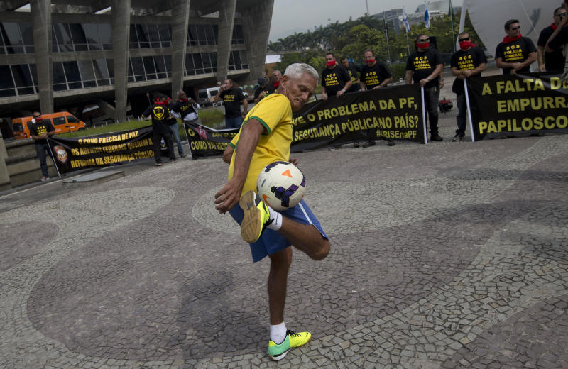 A Brazil soccer fan kicks a ball where federal police protest for better labor conditions outside the venue where Brazil's coach is announcing his squad for the upcoming international soccer tournament in Rio de Janeiro, Brazil, Wednesday, May 7, 2014. The team will mix talented young stars such as Neymar and Oscar with more experienced players such as Dani Alves, David Luiz, Thiago Silva and Hulk. Past stars such as Ronaldinho, Kaka and Robinho were left off the squad as expected. Federal police are threatening to go on strike during the international soccer tournament if their demands are not met. (AP Photo/Silvia Izquierdo)