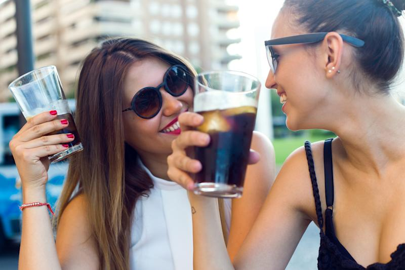 Two women drink soda while sitting outside.