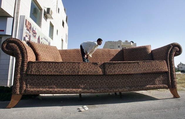 A Jordanian worker performs noon prayer on a huge sofa in Amman June 19, 2006. The sofa, measuring seven metres long and two metres tall, took about seventy metres of material and two weeks to complete. Its owner hopes it would be considered for the Guinness Book of Records for the biggest sofa in the world. REUTERS/Ali Jarekji