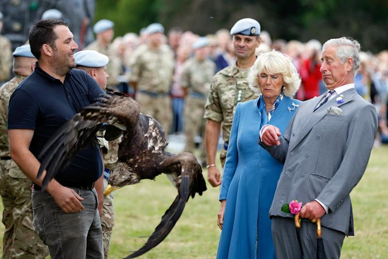 Camilla Parker Bowles and Prince Charles reacting to a bald eagle flapping its wings during their visit to the Sandringham Flower Show in King's Lynn, England, July 2015.