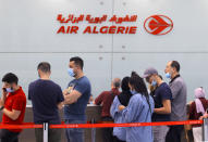 Travelers queue at the Houari Boumediene airport for a flight bound to Paris, Tuesday, June 1, 2021 in Algiers. Algeria has partially reopened its air borders Tuesday for the first time in over 15 months of the COVID-19 crisis. (AP Photo/Fateh Guidoum)