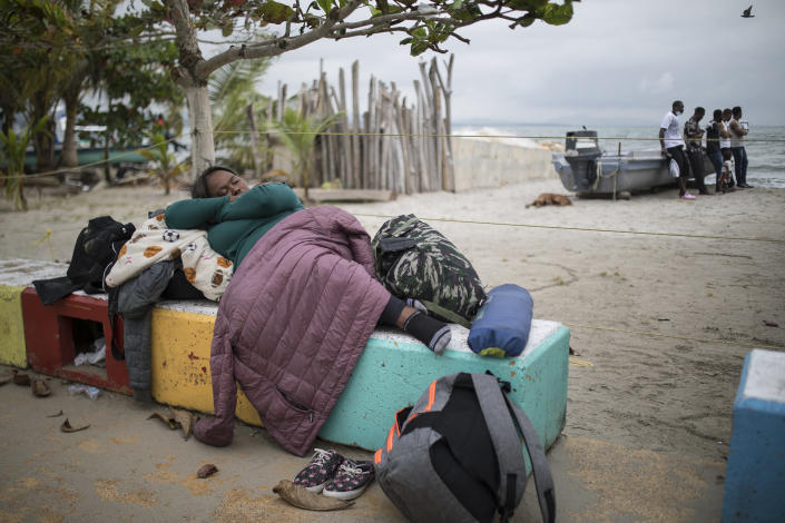 A migrant sleeps near the beach in Necocli, Colombia, at sunrise Thursday, July 29, 2021. Migrants have been gathering in Necocli as they move north towards Panama on their way to the U.S. border. (AP Photo/Ivan Valencia)
