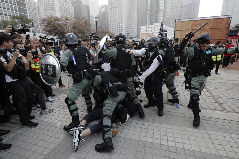 Riot policemen arrest protesters during a rally to show support for Uighurs and their fight for human rights in Hong Kong, Sunday, Dec. 22, 2019. (AP Photo/Lee Jin-man)