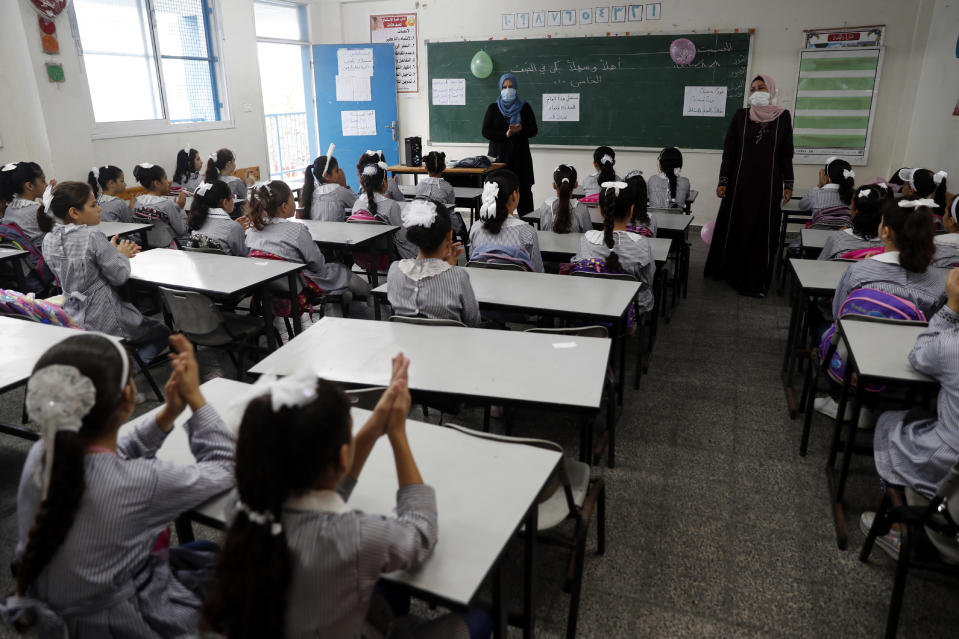 Teachers wear protective face masks while teaching class on the first day of the new school year at the United-Nation run Elementary School at the Shati refugee camp in Gaza City, Saturday, Aug. 8, 2020. Schools run by both Palestinian government and the U.N. Refugee and Works Agency (UNRWA) have opened almost normally in the Gaza Strip after five months in which no cases of community transmission of the coronavirus had been recorded. (AP Photo/Adel Hana)