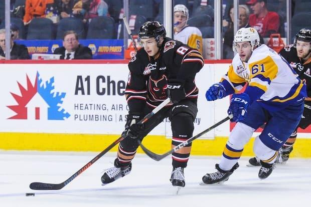 Vladislav Yeryomenko of the Calgary Hitmen, centre, carries the puck past Josh Paterson of the Saskatoon Blades during a 2018 WHL game. The hockey league says it will require players to be vaccinated this upcoming season. (Derek Leung/Getty Images - image credit)