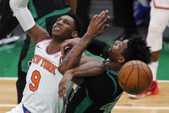 New York Knicks' RJ Barrett (9) and Boston Celtics' Marcus Smart (36) battle for the ball during the first half of an NBA basketball game, Sunday, Jan. 17, 2021, in Boston. (AP Photo/Michael Dwyer)