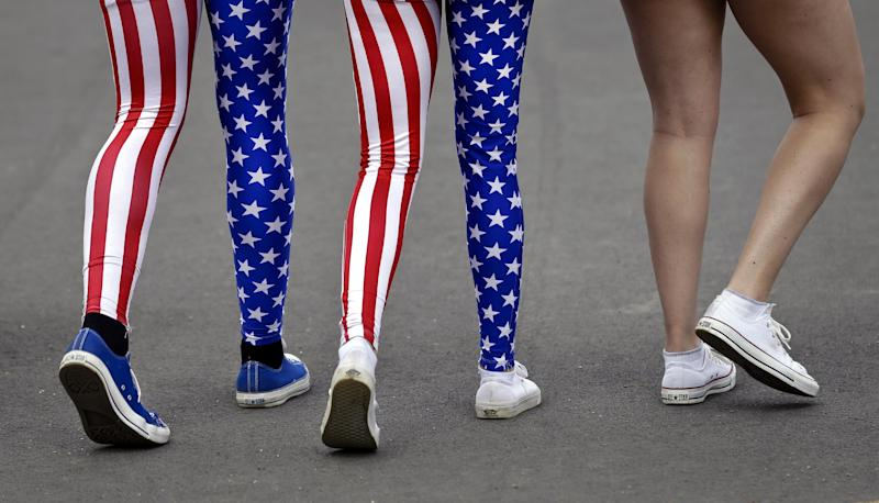 In this Thursday, Aug. 2, 2012 photo, Nick Miller, left, and his sister Kendall Miller, center, from San Francisco, wear leotards in the colors of the United States national flag as they walk with a friend through Olympic Park at the 2012 Summer Olympics, in London. Patriotism and the games have always gone together, but gone are the days when one just waved a flag. Now flags are worn, seen all over London and especially at Olympic Park and other spots where the games are being played. (AP Photo/Ben Curtis)