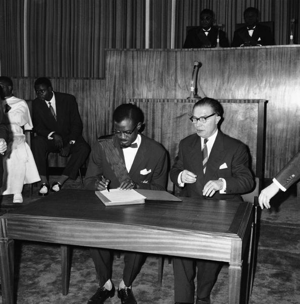 FILE - In this June 30, 1960 file photo, first Prime Minister of the Congo Patrice Lumumba, left, signs the act of independence of the Congo, with Prime Minister of Belgium Gaston Eyskens, right, in Leopoldville, the capital before it was later renamed in 1966 to Kinshasa, in Congo. On Tuesday, June 30, 2020 Congo is marking the 60th anniversary of achieving independence from the colonial rule of Belgium. (AP Photo/Jean Jacques Levy, File)