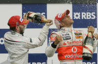 FILE - In this Sunday, June 10, 2007 file photo, Sauber driver Nick Heidfeld, left, of Germany, and McLaren Mercedes driver Lewis Hamilton, right, of Britain, celebrate after Hamilton won the Canadian Grand Prix Formula One race at the Circuit Gilles Villeneuve in Montreal, Canada. British driver Lewis Hamilton made Formula One history on Sunday, Oct. 25, 2020 winning the Portuguese Grand Prix for a 92nd win to move one ahead of German great Michael Schumacher. (AP Photo/Darron Cummings, file)