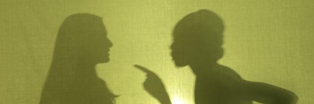 Silhouette of woman scolding another woman.