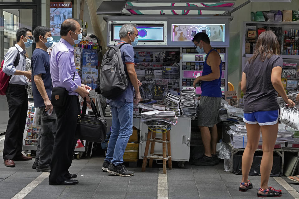 People queue up to buy Apple Daily at a downtown street in Hong Kong Friday, June 18, 2021. The pro-democracy paper increased its print run to 500,000 copies on Friday, a day after police arrested five top editors and executives and froze $2.3 million in assets linked to the media company. (AP Photo/Vincent Yu)