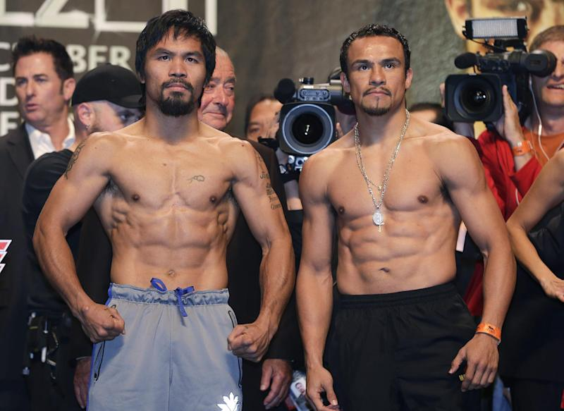 Manny Pacquiao, left, and Juan Manuel Marquez pose for photos during the weigh-in for their welterweight fight, Friday, Dec. 7, 2012, in Las Vegas. Pacquiao and Marquez are scheduled to face off on Saturday in their fourth fight. (AP Photo/Julie Jacobson)