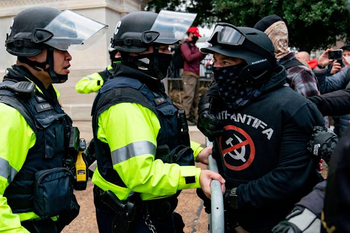 A protester, who claims to be a member of the Proud Boys, confronts police officers as supporters of former President Donald Trump protest outside the U.S. Capitol on Jan. 6, 2021, in Washington.