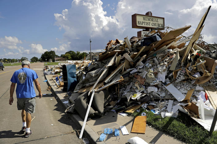 In Port Arthur, Texas, on Sept. 25, Wayne Christopher walks by debris collected after the devastation of Hurricane Harvey, which was piled outside the church that he has attended his whole life. (Photo: David Goldman/AP)
