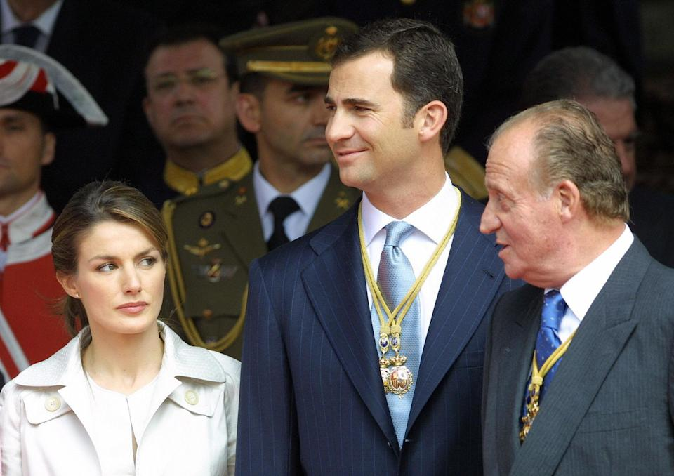 MADRID, SPAIN:  Prince Felipe (C) smiles as his father, Spain's King Juan Carlos I (R) talks to Prince Felipe's fiancee Letizia Ortiz (L), 22 April 2004 in the Spanish city of Madrid, during a military parade to celebrate the opening of the Spanish Parliament's eight legislature. Expressing
