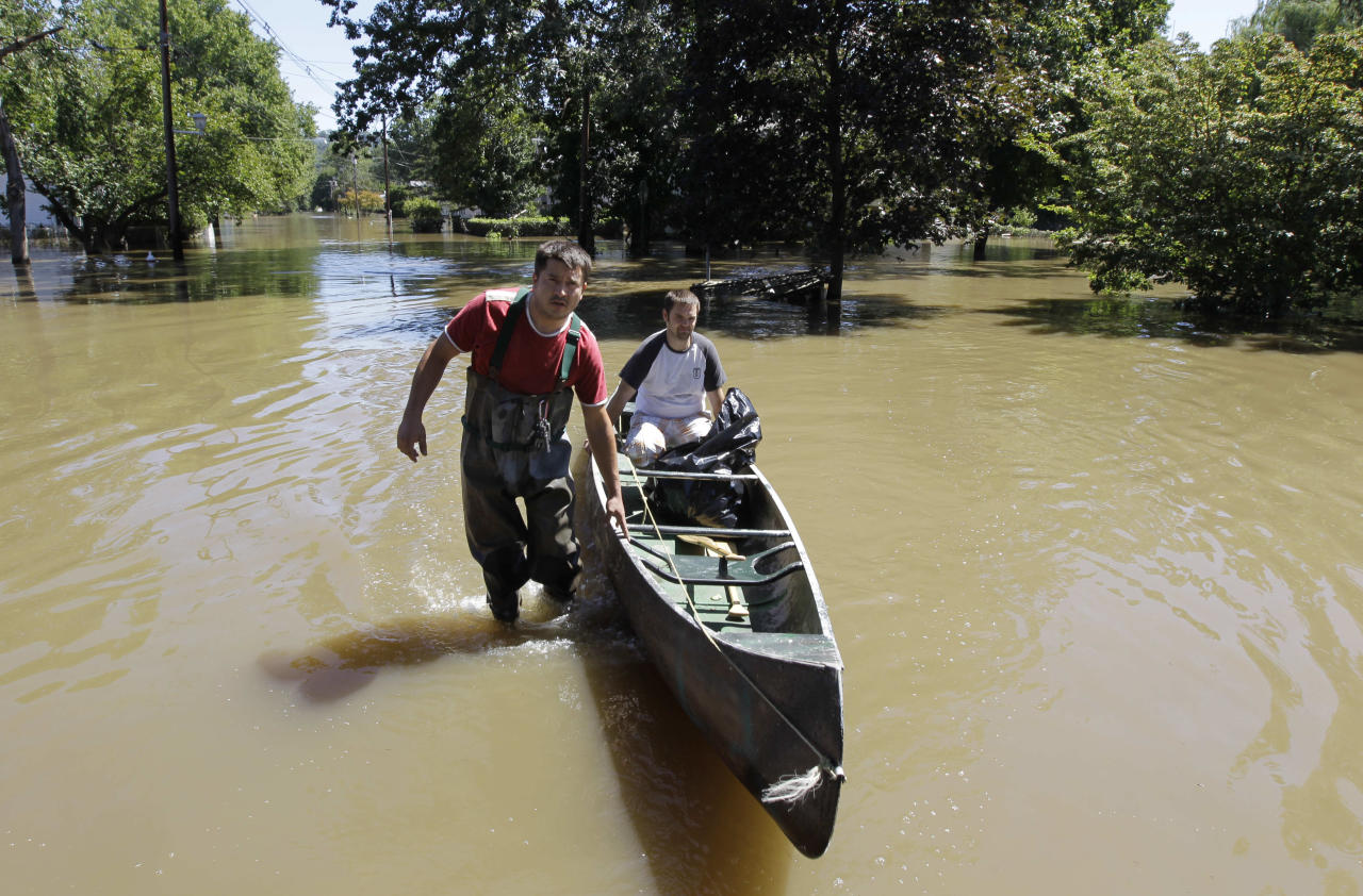 Gino Borova, left, gives a canoe ride to his neighbor, Tom Soboleski, as they made their way through floodwaters after surveying their houses in Pompton Lakes, N.J., where the Ramapo River crested in the aftermath of Hurricane Irene, Monday, Aug. 29, 2011. Pompton Lakes is surrounded by three rivers and was seeing serious flooding Monday. Record crests were expected in the area. (AP Photo/Julio Cortez)