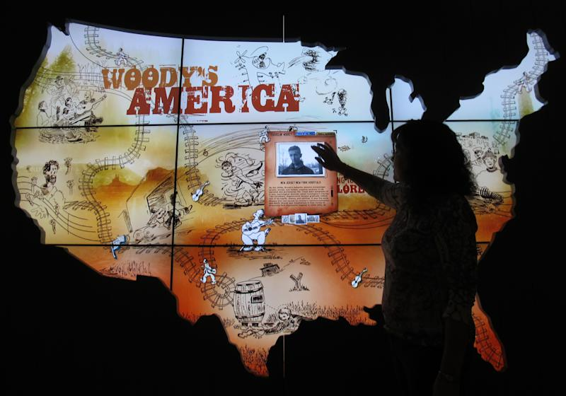 In this April 25, 2013, photo Deana McCloud, of the Woody Guthrie Center, tries out the Woody's America interactive map at the Woody Guthrie Center in Tulsa. The 12,000 square-foot center, which opens to the public on Saturday, features many interactive exhibits chronicling the life and work of Woody Guthrie and is home to the folk singer's archives. (AP Photo/Justin Juozapavicius)