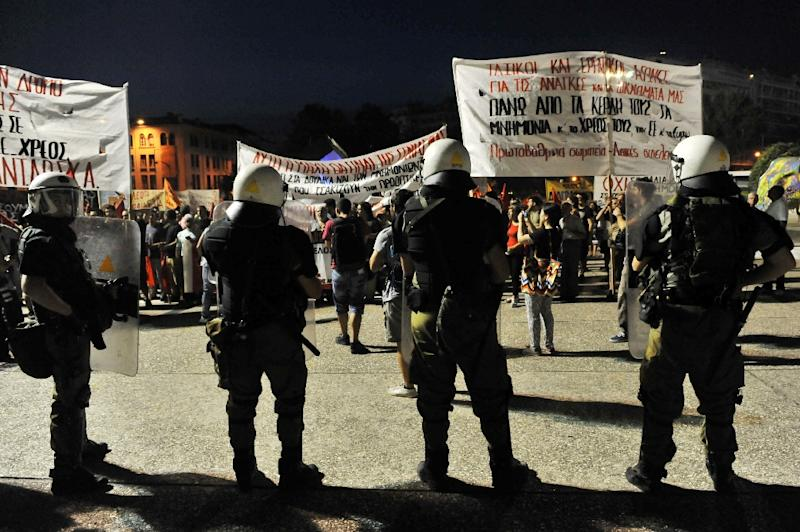 Police watch demonstrators taking part in a protest against government austerity measures and reforms in Thessaloniki on September 5, 2015