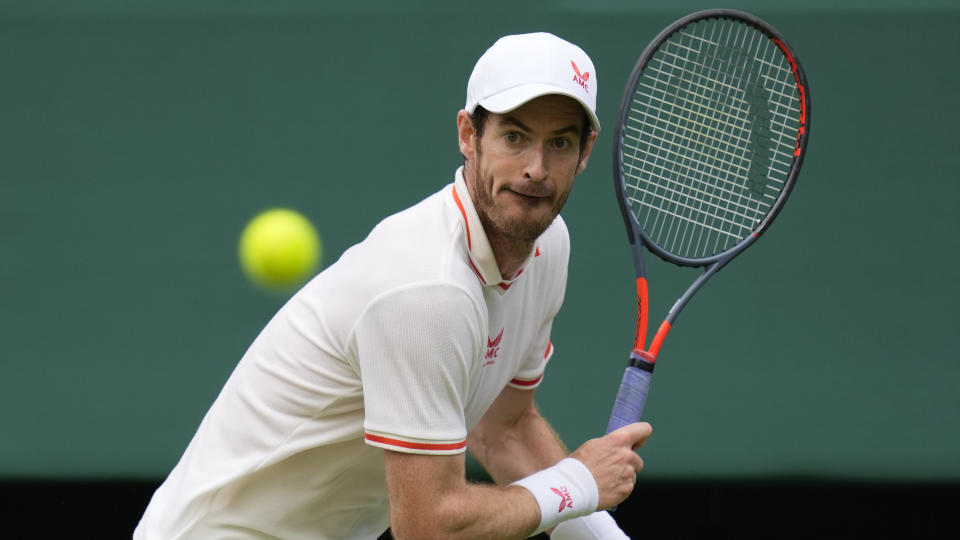 Britain's Andy Murray returns the ball to Georgia's Nikoloz Basilashvili during the men's singles match on day one of the Wimbledon Tennis Championships in London, Monday June 28, 2021. (AP Photo/Kirsty Wigglesworth)