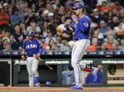 Texas Rangers' Ronald Guzman, right, reacts as he crosses the plate on his home run during the eighth inning of the team's baseball game against the Houston Astros on Wednesday, Sept. 18, 2019, in Houston. (AP Photo/Michael Wyke)