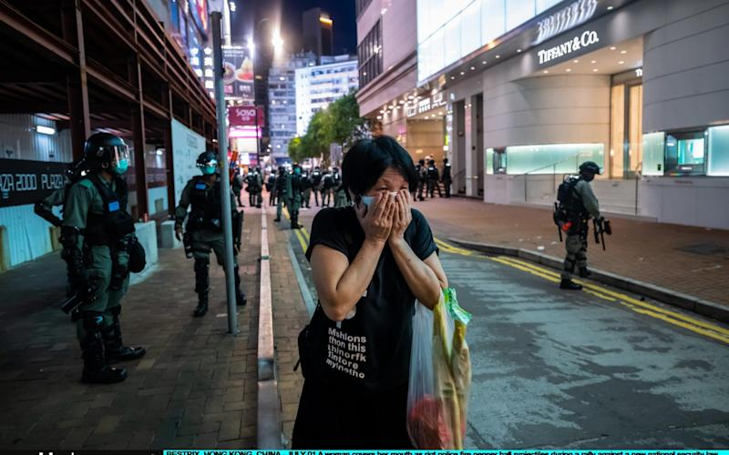 A woman covers her mouth as riot police fire pepper ball projectiles during a rally against a new national security law on Wednesday's 23rd anniversary of the city's handover from Britain to China - Billy HC Kwok/Getty