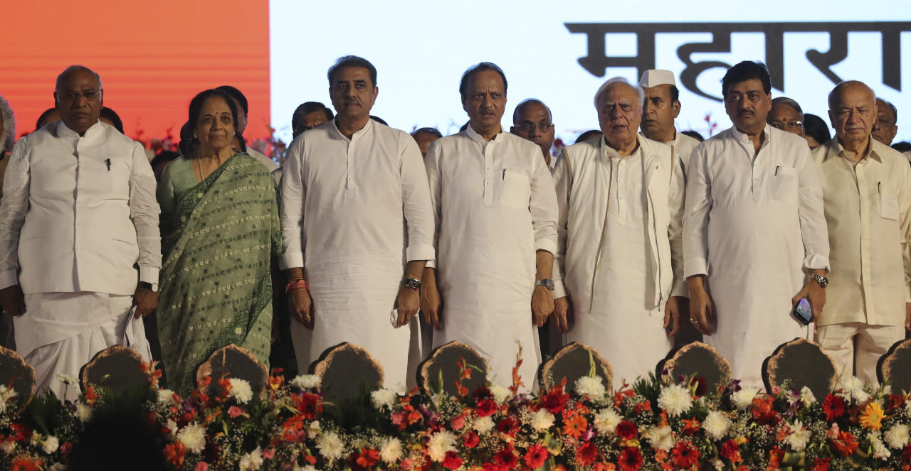 Leaders of various political parties stand for the national anthem during a swearing-in-ceremony of Shiv Sena party leader Uddhav Thackeray as chief minister of Maharashtra state during a swearing-in-ceremony in Mumbai, Thursday, Nov. 28, 2019. Supporters of the Shiv Sena, Nationalist Congress Party (NCP) and the Congress party thronged Shivaji Park to watch their leaders take oath of office. (AP Photo/Rafiq Maqbool)