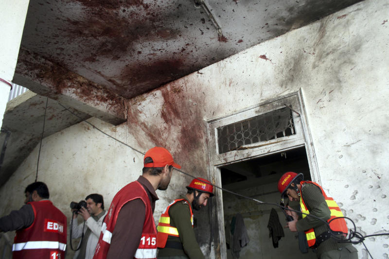 Pakistani rescue workers examine the site of attack in a police station in Peshawar, Pakistan on Friday, Feb 24, 2012. Suicide bombers armed with assault rifles and grenades attacked a large police station in the northwestern Pakistan city of Peshawar early Friday, killing three officers in an assault authorities said was likely in revenge for offensives against nearby strongholds.(AP Photo/Mohammad Sajjad)