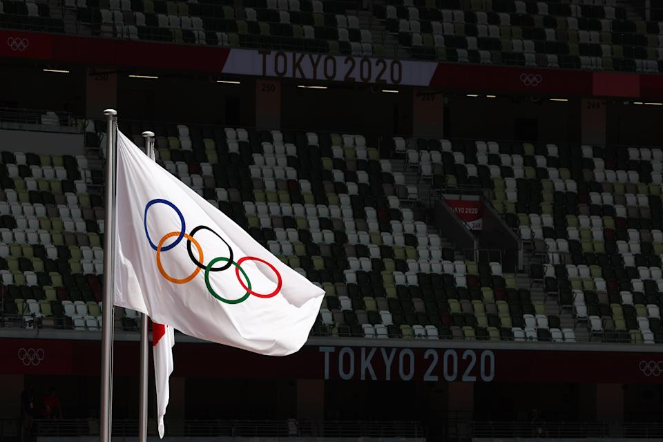 The Olympic and Japanese flags fly in front of rows of empty seats in the Olympic Stadium (Getty Images)