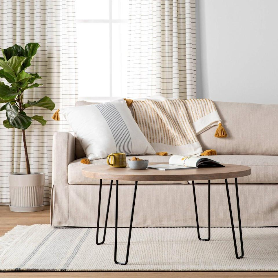<p>We're into the sleek look of the <span>Hearth &amp; Hand with Magnolia Wood &amp; Wire Coffee Table</span> ($160). The round design and compact size would work well in a smaller space.</p>