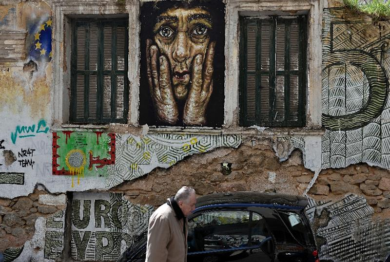 A man walks past a building adorned with graffitis and slogans reading 'Euro' in central Athens, Greece, on March 19, 2015 (AFP Photo/Louisa Gouliamaki)