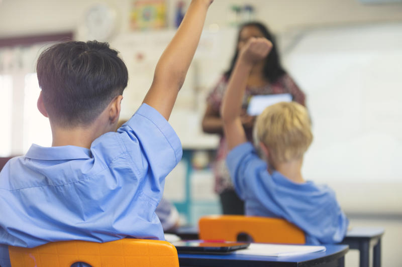 Pictured is two school students raising their arms in blue shirts in a classroom.