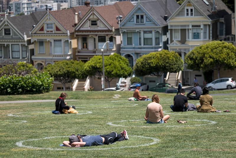 People sit on the grass in circles drawn to promote social distancing at Alamo Square in San Francisco, California, U.S., on Thursday, June 11, 2020.