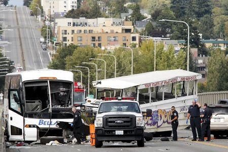 Personnel remove the bodies of victims from the scene of a crash between a Ride the Ducks vehicle and a charter bus on Aurora Bridge in Seattle