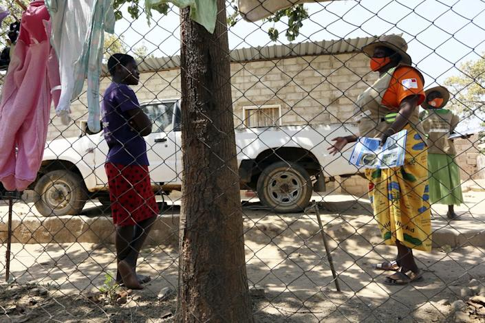 Community health worker, Rosemary Rambire, right, speaks to a young girl during a COVID-19 awareness campaign in Chitungwiza, on the outskirts of Harare, Zimbabwe, Wednesday, Sept. 23, 2020. (AP Photo/Tsvangirayi Mukwazhi)