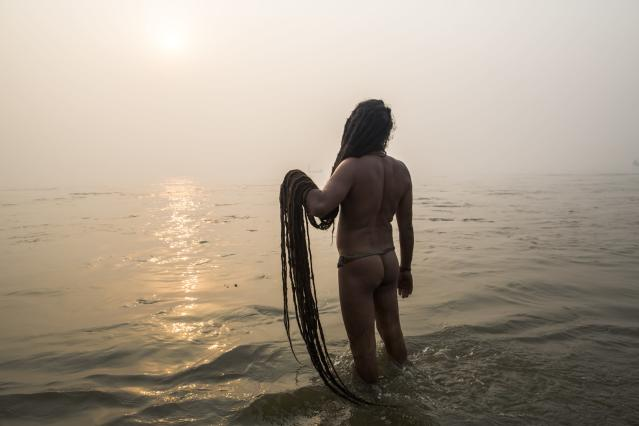 ALLAHABAD, INDIA - JANUARY 14: A naga sadhu prays holding his dreadlocks as he bathes in the waters of the holy Ganges river during the auspicious royal bathing day of Makar Sankranti of the start of the Maha Kumbh Mela on January 14, 2013 in Allahabad, India. The Maha Kumbh Mela, believed to be the largest religious gathering on earth is held every 12 years on the banks of Sangam, the confluence of the holy rivers Ganga, Yamuna and the mythical Saraswati. The Kumbh Mela alternates between the cities of Nasik, Allahabad, Ujjain and Haridwar every three years. The Maha Kumbh Mela celebrated at the holy site of Sangam in Allahabad, is the largest and holiest, celebrated over 55 days, it is expected to attract over 100 million people. (Photo by Daniel Berehulak/Getty Images)