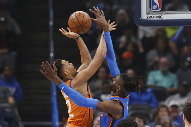Phoenix Suns forward Elie Okobo (2) shoots as Oklahoma City Thunder center Nerlens Noel defends during the first half of an NBA basketball game Friday, Dec. 20, 2019, in Oklahoma City. (AP Photo/Sue Ogrocki)
