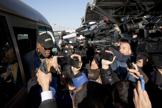 Former NBA star Dennis Rodman, left, arrives at the capital airport for a flight to North Korea, in Beijing, China, Thursday, Dec. 19, 2013. Rodman is flying to North Korea to help train the national team and renew his friendship with the North's young leader Kim Jong Un, a visit unaffected by the recent execution of Kim's uncle in a dramatic political purge. (AP Photo/Ng Han Guan)