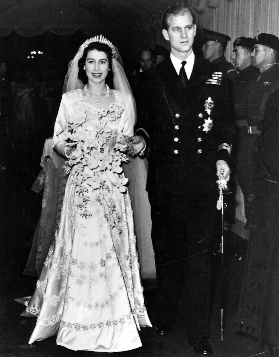 """<p>When Elizabeth married in 1947, her wedding dress was designed to be a symbol of the nation, royal wedding gown curator Joanna Marschner told <em><a href=""""https://news.nationalgeographic.com/news/2011/04/pictures/110428-royal-wedding-dress-kate-middleton-prince-william-gown-designed/"""" rel=""""nofollow noopener"""" target=""""_blank"""" data-ylk=""""slk:National Geographic"""" class=""""link rapid-noclick-resp"""">National Geographic</a></em>. With everything still rationed in post-WWII Britain, the idea was to send <a href=""""https://www.rct.uk/about/news-and-features/the-queens-wedding-and-coronation-dresses-to-be-displayed-together-for-the#/"""" rel=""""nofollow noopener"""" target=""""_blank"""" data-ylk=""""slk:a message of national renewal and hope"""" class=""""link rapid-noclick-resp"""">a message of national renewal and hope</a> for the future. </p>"""