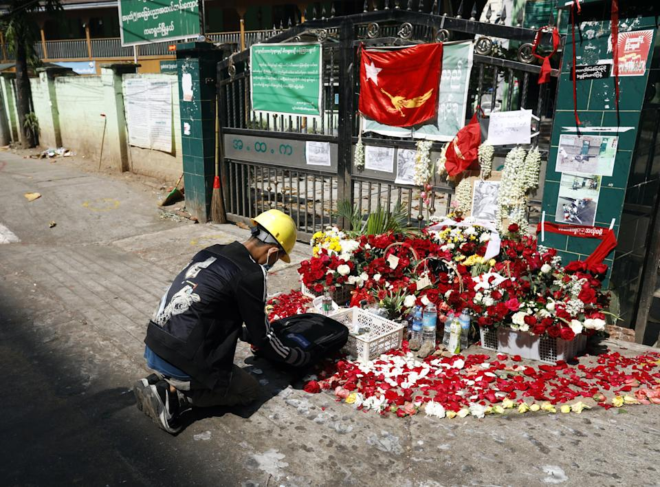 <p>A man lays flowers at a memorial for Nyi Nyi Aung Htet Naing, a 23-year-old protester who was killed during a crackdown on anti-coup protesters in Yangon, Myanmar </p> (EPA)