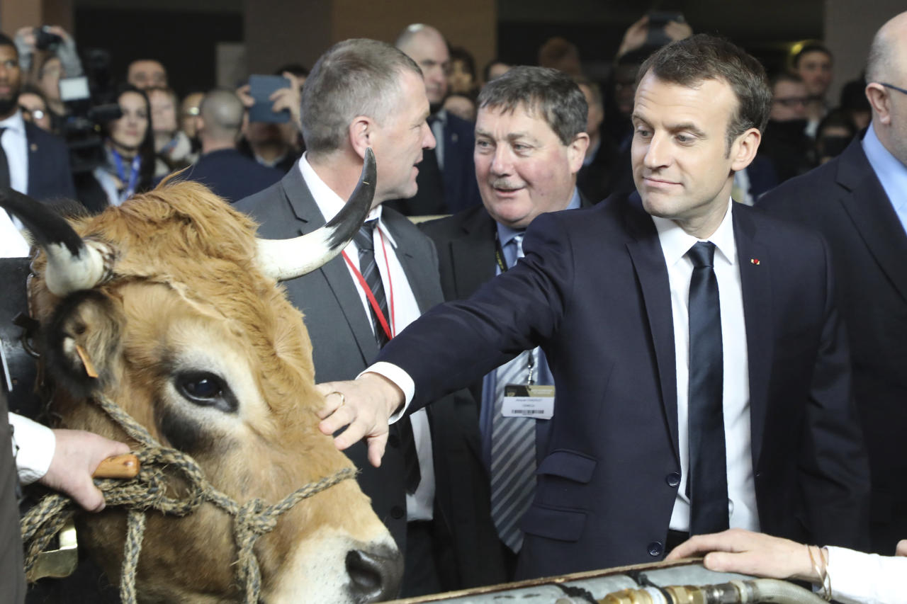 <p> French President Emmanuel Macron, right, visits the 55th International Agriculture Fair at the Porte de Versailles exhibition center in Paris, France, Saturday, Feb. 24, 2018. The fair, featuring farm animals, food and agriculture industry, will last until March 4, 2018. (Ludovic Marin/Pool Photo via AP) </p>